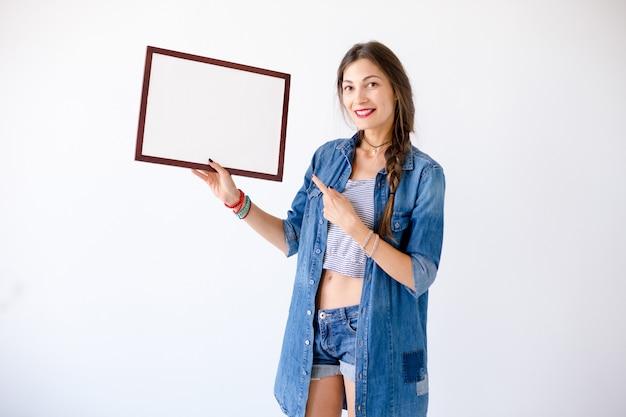 Przytulna kobieta pokazuje pusty biały plakat lub plakat