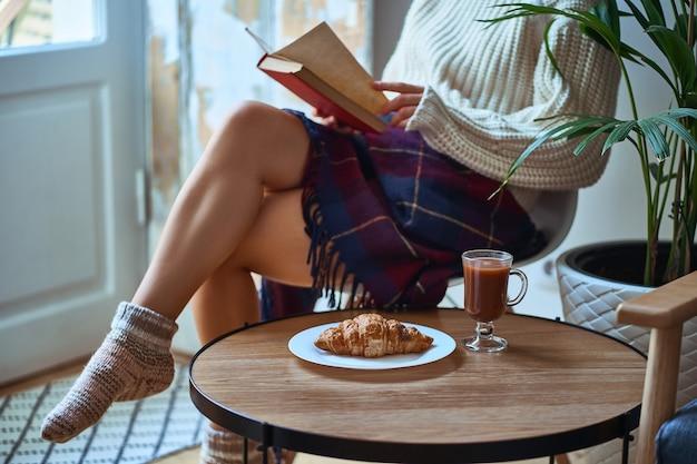 Przytulna kobieta w ciepłym białym swetrze, robionych na drutach skarpetkach i przykryta kocem czytająca książkę i ciesząca się komfortową domową atmosferą i wygodną rozrywką