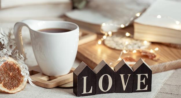 Przytulna kompozycja do domu z ozdobnym słowem miłość na rozmytym tle z bokeh.