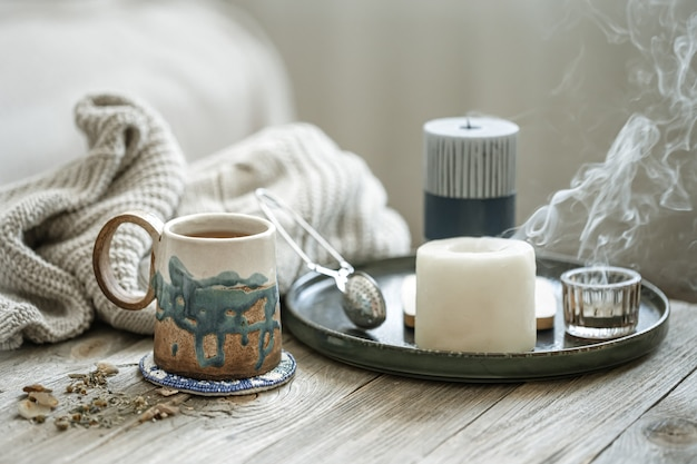 Przytulna kompozycja z ceramicznym kubkiem, świecami i dzianinowym elementem