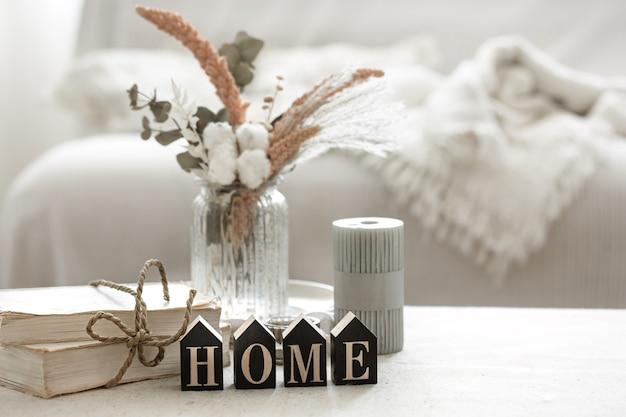 Przytulna kompozycja z detalami wystroju wnętrza i dekoracyjnym słowem home.