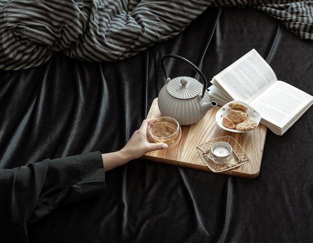 Przytulna kompozycja z filiżanką herbaty w kobiecych dłoniach, ciasteczkami i książką w łóżku.
