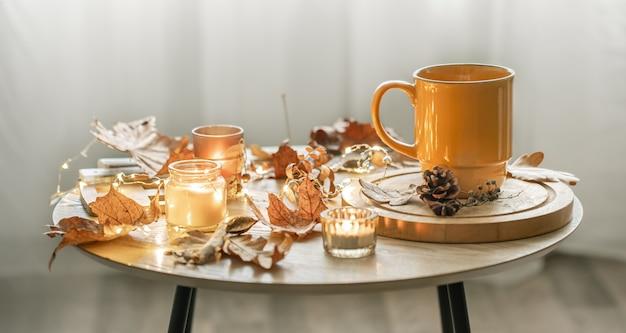 Przytulna kompozycja z filiżanką, świecami i jesiennymi liśćmi we wnętrzu.