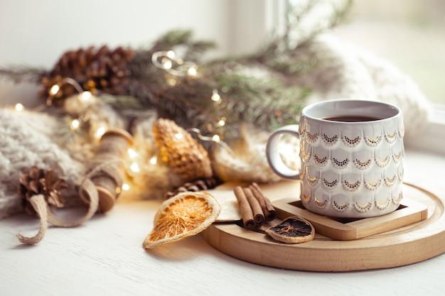 Przytulna kompozycja ze świątecznym kubkiem z gorącym napojem i cynamonem na rozmytym tle. domowa zimowa przytulność