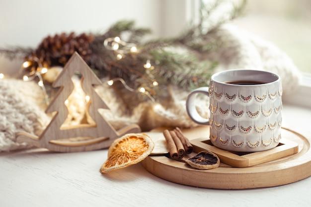 Przytulna kompozycja ze świątecznym kubkiem z gorącym napojem i cynamonem na rozmytym tle. koncepcja przytulności domu zima.