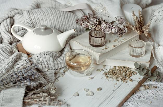 Przytulna, lekka martwa natura ze świecami, filiżanką herbaty, czajnikiem i kwiatami jako wystrój.