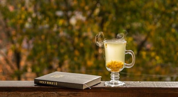 Przytulna martwa natura: filiżanka gorącej herbaty z rokitnika i książka biblia na parapecie w stylu vintage na tle ciepłego krajobrazu z zewnątrz.