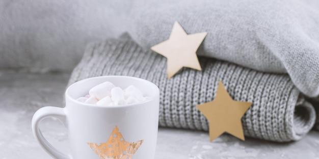 Przytulna martwa natura z filiżanką z marshmallows i dzianinowymi swetrami i papierowymi złotymi gwiazdami