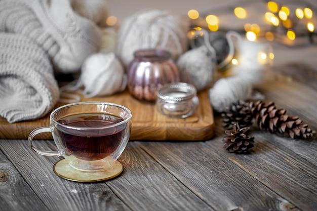Przytulna martwa natura z herbatą i elementami dekoracyjnymi, świecącymi światłami.