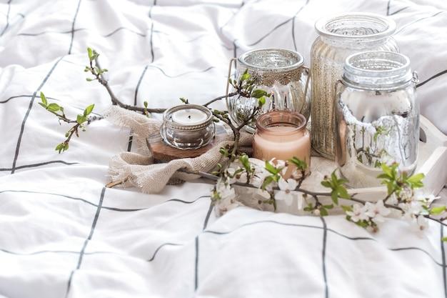 Przytulna martwa natura z różnymi świecami w łóżku