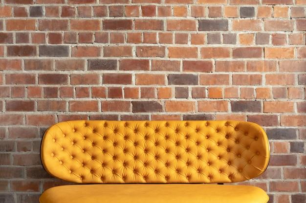 Przytulna nowoczesna sofa obok ceglanego muru