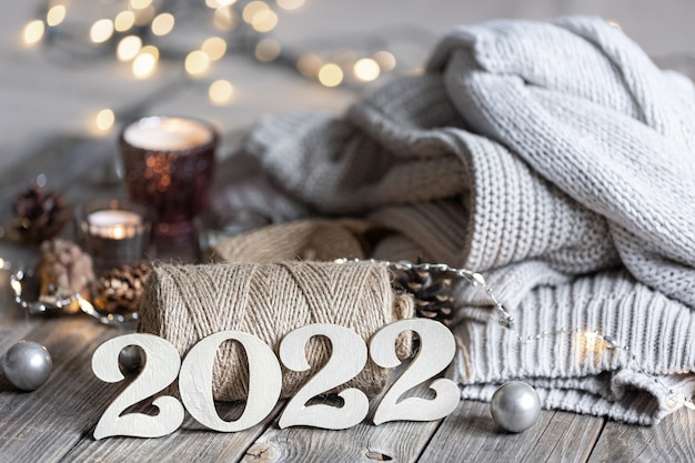 Przytulna noworoczna kompozycja z dekoracyjnymi numerami 2022, dzianinowymi elementami i światłami bokeh.