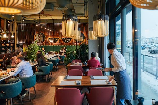Przytulna restauracja z ludźmi i kelnerem