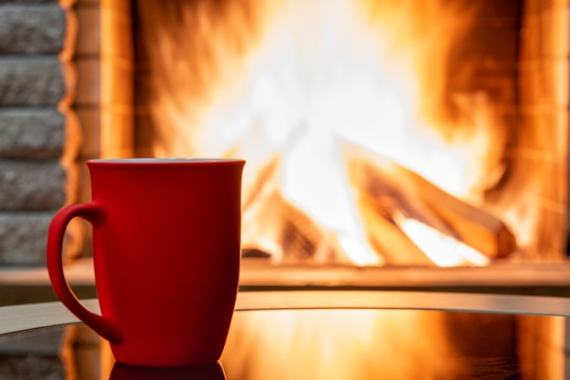 Przytulna scena kominkowa i duży kubek herbaty, odbicie od ognia na szklanym stole.