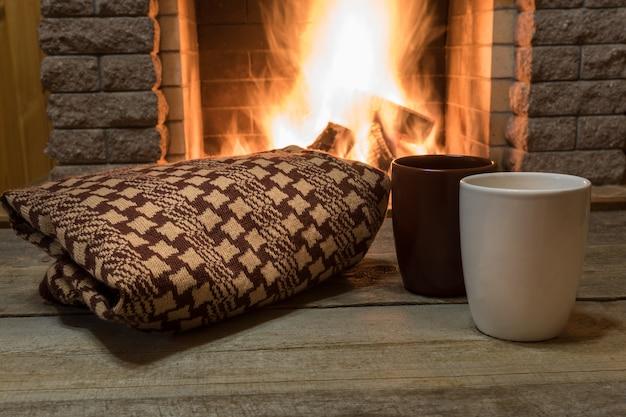 Przytulna scena przy kominku z kubkami gorącej herbaty i ciepłym szalikiem.