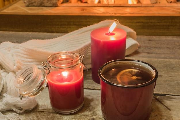 Przytulna scena przy kominku z kubkiem gorącej herbaty, ciepłym szalikiem i świecami.