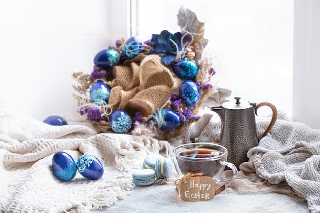 Przytulna scena wielkanocna, martwa wiosna. śniadanie z herbatą i makaronikami deserowymi