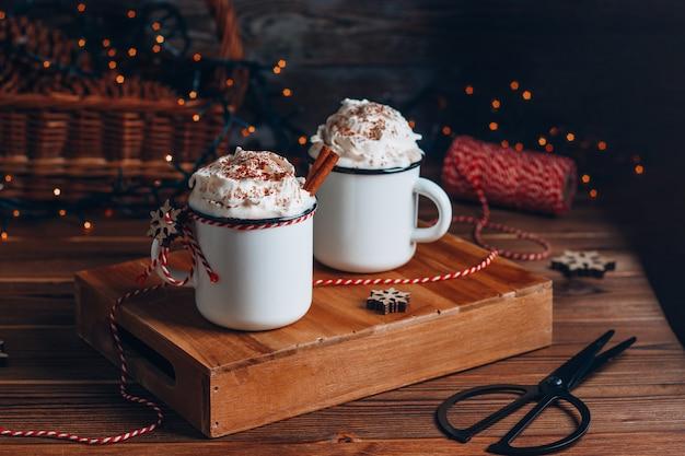 Przytulna świąteczna kompozycja. dwa kubki z gorącymi napojami, czekoladą z bitą śmietaną i cynamonem na ciemnym drewnie. słodkie przysmaki na chłodne zimowe dni.