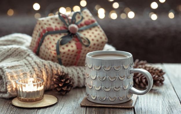 Przytulna świąteczna kompozycja z filiżanką i świątecznymi detalami dekoracyjnymi na rozmytym ciemnym tle z bokeh.