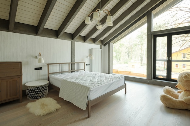 Przytulna sypialnia z dużym misiem, małym stolikiem nocnym z dywanem i podwójnym łóżkiem w domku ze szklaną ścianą