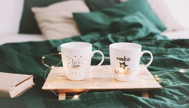 Przytulna sypialnia z kubkami do kawy w łóżku
