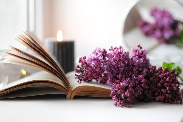 Przytulna wiosenna atmosfera w domu z bzem, książką i świecą. czas kwitnienia bzu.