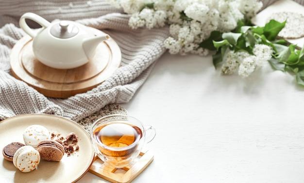 Przytulna wiosenna kompozycja z filiżanką herbaty, czajniczkiem, francuskimi makaronikami, liliowym kolorem na lekko rozmytym stole.