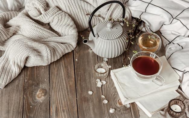 Przytulna wiosenna martwa natura ze świecami, herbatą, czajnikiem na drewnianej powierzchni w stylu rustykalnym.