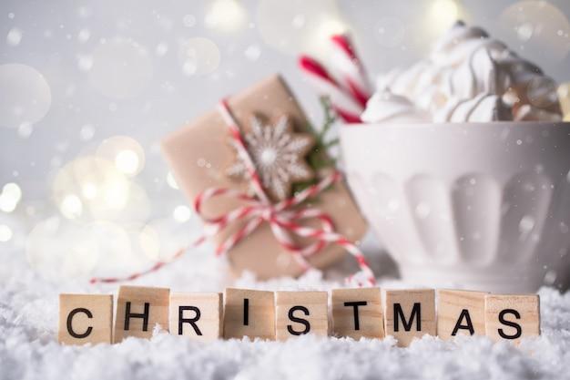 Przytulna zimowa kompozycja z filiżanką gorącej czekolady z ciasteczkami z piernika i prezentem świątecznym. świąteczne słowo z liter