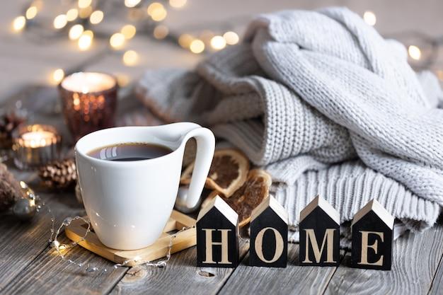 Przytulna zimowa kompozycja z filiżanką herbaty, ozdobnym słowem home, dzianinowymi elementami i światłami bokeh.