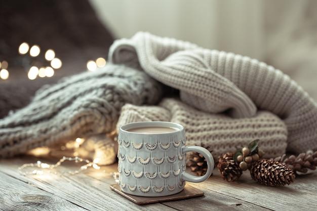 Przytulna zimowa kompozycja z filiżanką i detalami dekoracyjnymi na rozmytym tle.
