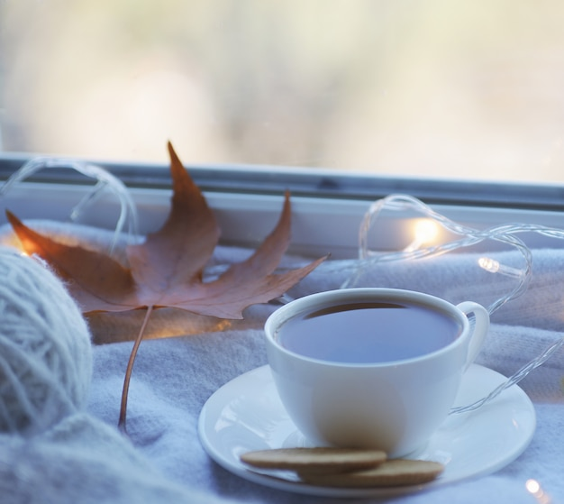 Przytulna zimowa martwa natura: kubek gorącej herbaty i książka z ciepłą kratą na parapecie na tle śniegu z zewnątrz.