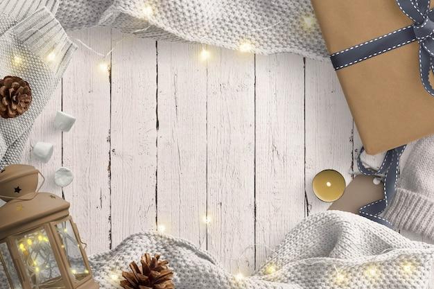 Przytulna zimowa scena z bajkowymi światłami, latarnią, prezentem, szyszkami i wełnianym swetrem