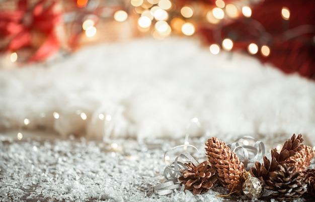 Przytulna zimowa świąteczna ściana ze śniegiem i ozdobnymi szyszkami kopiować przestrzeń.