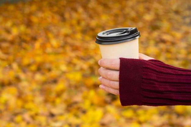 Przytulne, ciepłe zdjęcie rzemieślniczego kubka gorącej kawy w dłoni na tle opadłych żółtych liści.