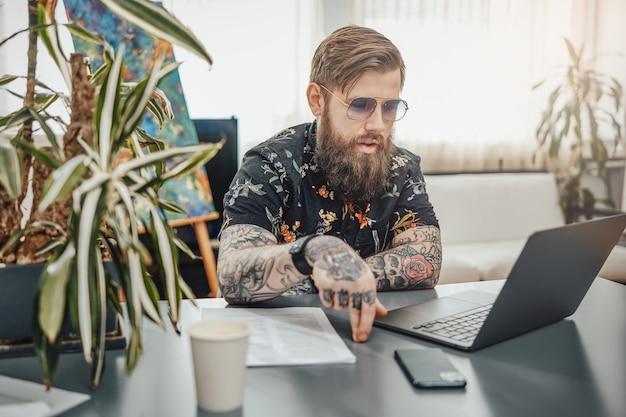 Przytulne domowe biuro i praca zdalna. mężczyzna z brodą i wytatuowanym ciałem ubrany w stylowe ubrania, wykonujący swoją pracę na laptopie w przytulnym pokoju.