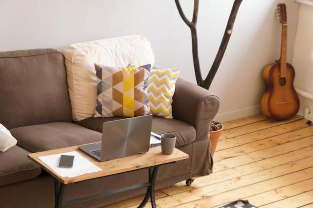 Przytulne domowe miejsce pracy freelancera, praca zdalna z domu. laptop, smartfon, notatnik, długopis leżą na stole przed brązową sofą na tle wyposażenia domu