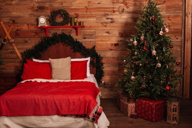 Przytulne duże podwójne łóżko obok choinki w wakacyjny wieczór