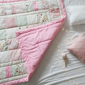 Przytulne łóżeczko dziecięce z patchworkowym kocem
