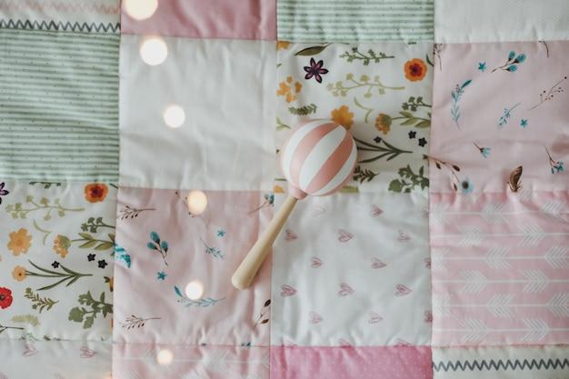 Przytulne łóżeczko dziecięce z różowym kocykiem patchworkowym