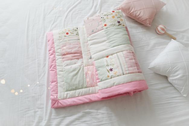 Przytulne łóżeczko dziecięce z różowym patchworkowym kocem. pościel dla niemowląt. pościel i tekstylia dla przedszkola. czas drzemki i snu.
