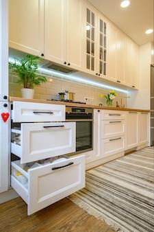 Przytulne, nowoczesne wnętrze kuchni, niektóre szuflady wysunięte