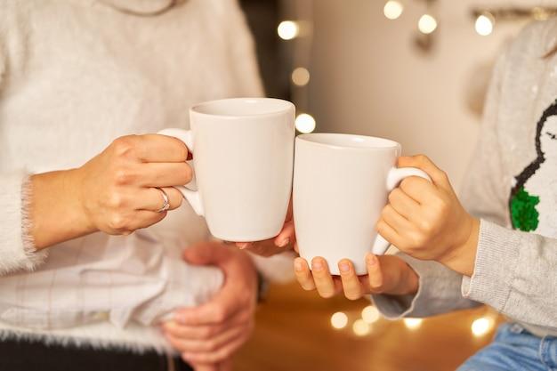 Przytulne, przyjazne rodzinne środowisko świąteczne w domu. mama i córka piją gorącą herbatę. zbliżenie białych filiżanek herbaty w ręce.