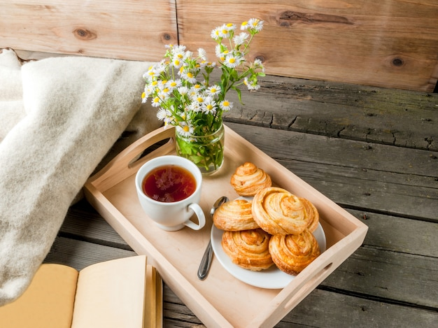 Przytulne śniadanie na wiosnę lub wczesną jesienią herbatę, świeżo upieczone bułeczki i bukiet stokrotki i fascynująca książka. skopiuj miejsce