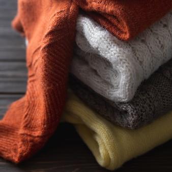 Przytulne swetry w jesiennych kolorach na brązowym drewnianym tle. miejsce na twój tekst.
