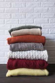 Przytulne swetry w jesiennych kolorach na brązowym drewnianym tle.
