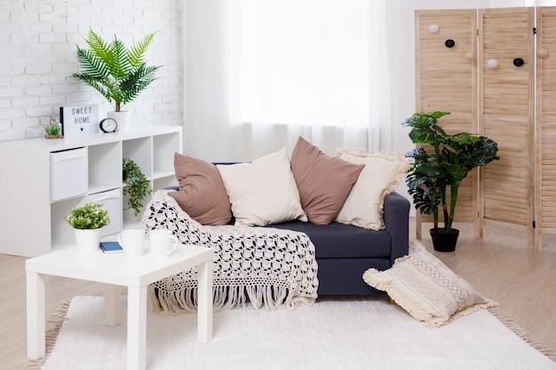 Przytulne tło domu - jasne wnętrze salonu z sofą, stołem, składanym parawanem i doniczkami
