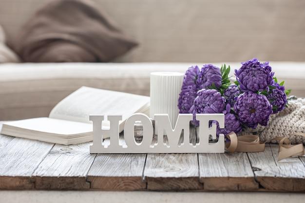 Przytulne tło z ozdobnym słowem do domu, bukietem chryzantemy, książką i świecą.