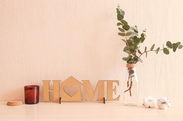 Przytulne wnętrze domu. dekor drewniany z napisem home, wazon z gałązkami eukaliptusa, świeca zapachowa