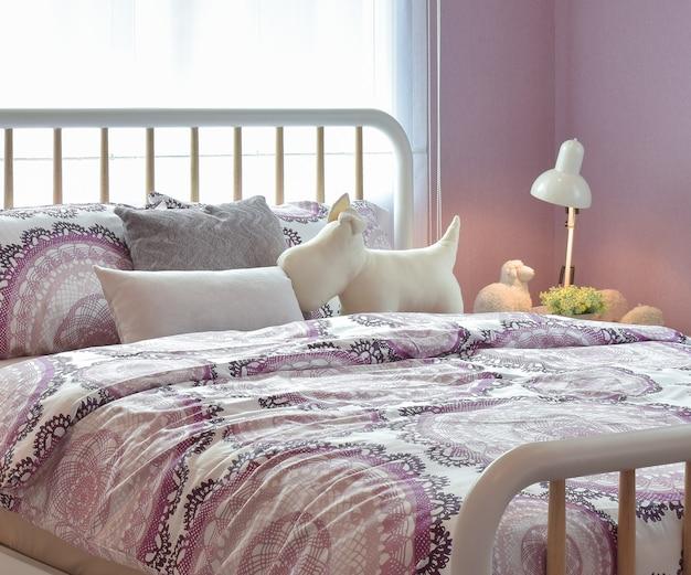 Przytulne wnętrze sypialni z poduszkami i lampką do czytania na stoliku nocnym